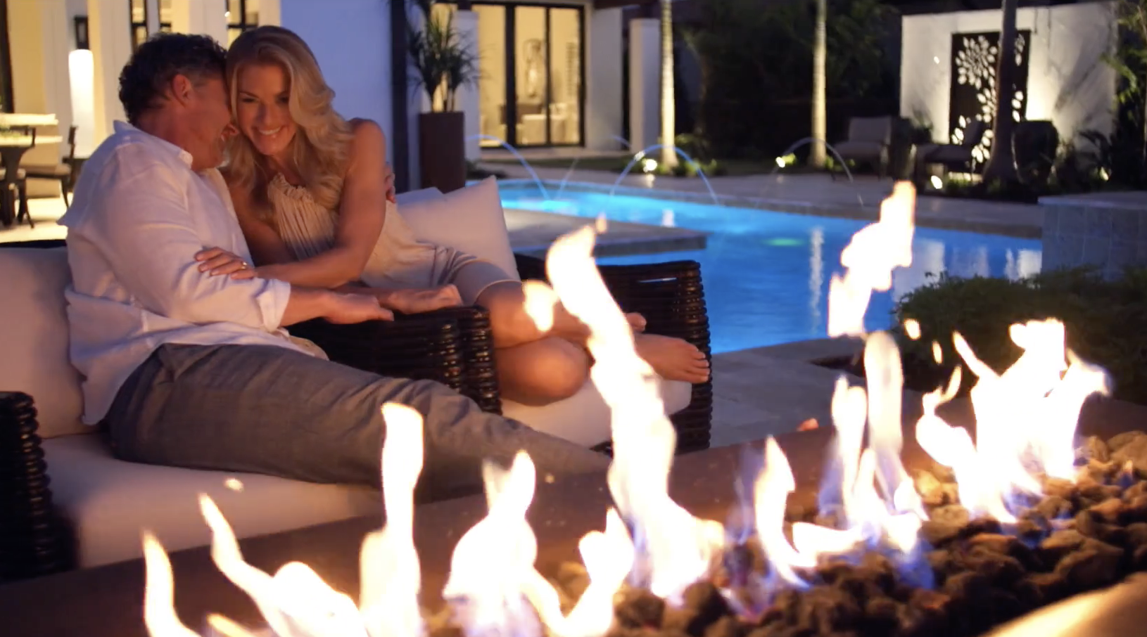 couple relaxing fireside by the pool in Naples, Florida